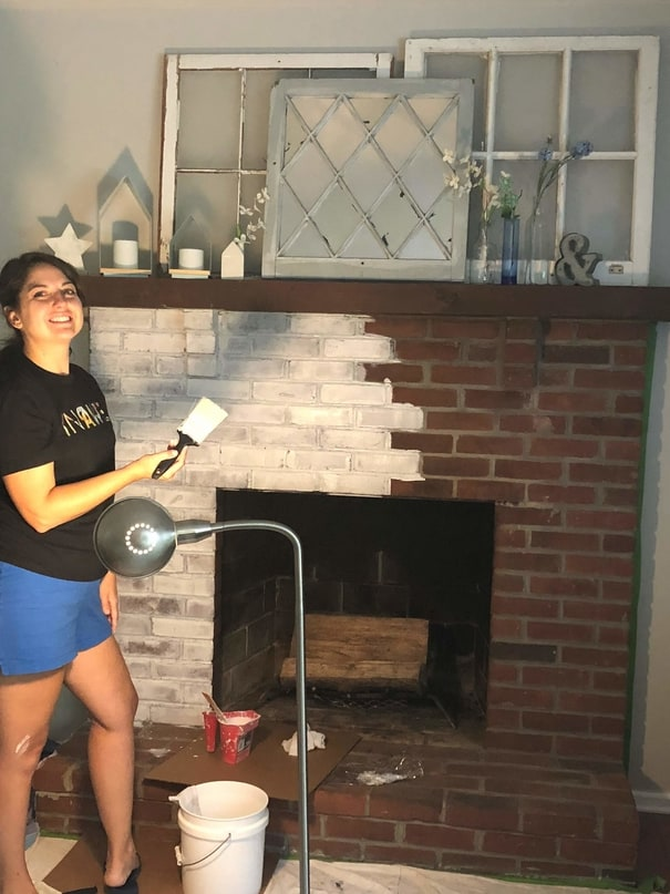 Woman painting fireplace with white paint