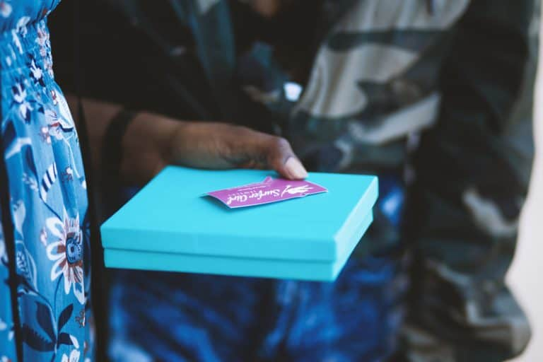 Woman holding gift card and gift box