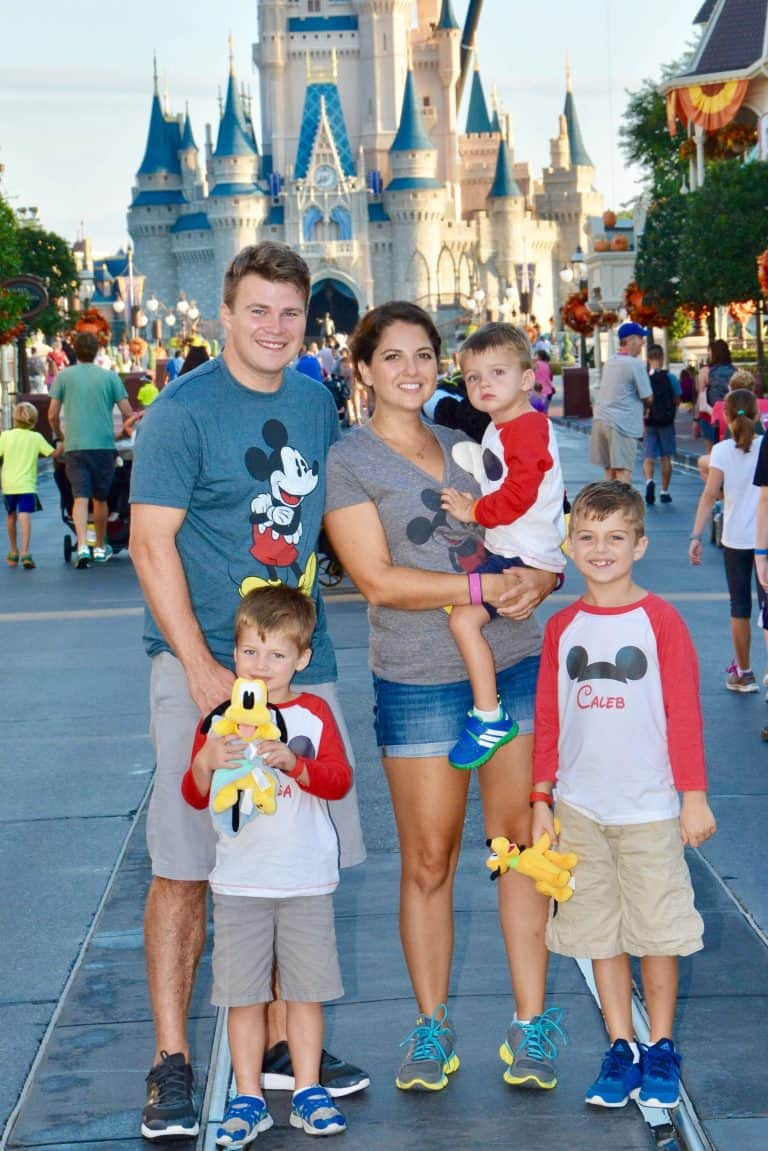 Family in Mickey shirts in front of Cinderella Castle in Magic Kingdom